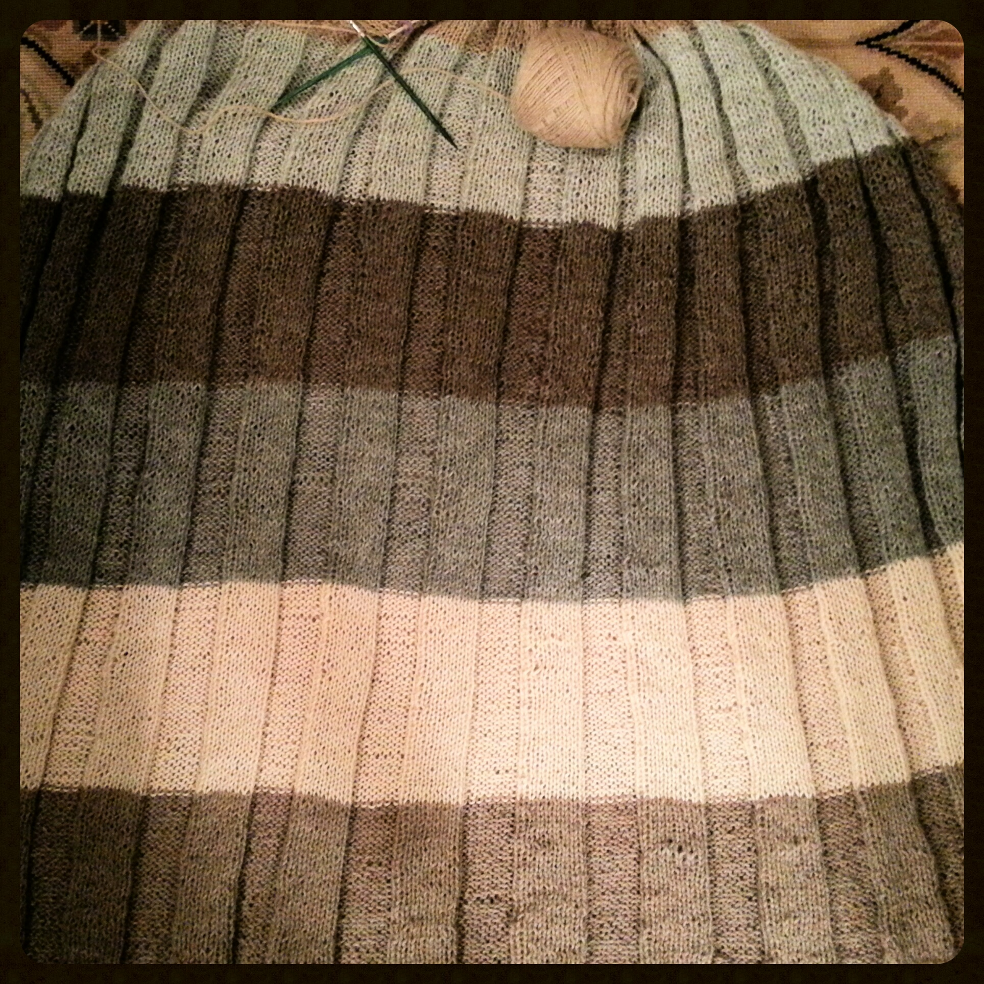 Six shades of undyed lace-weight yarn knitted into a large, striped stole.